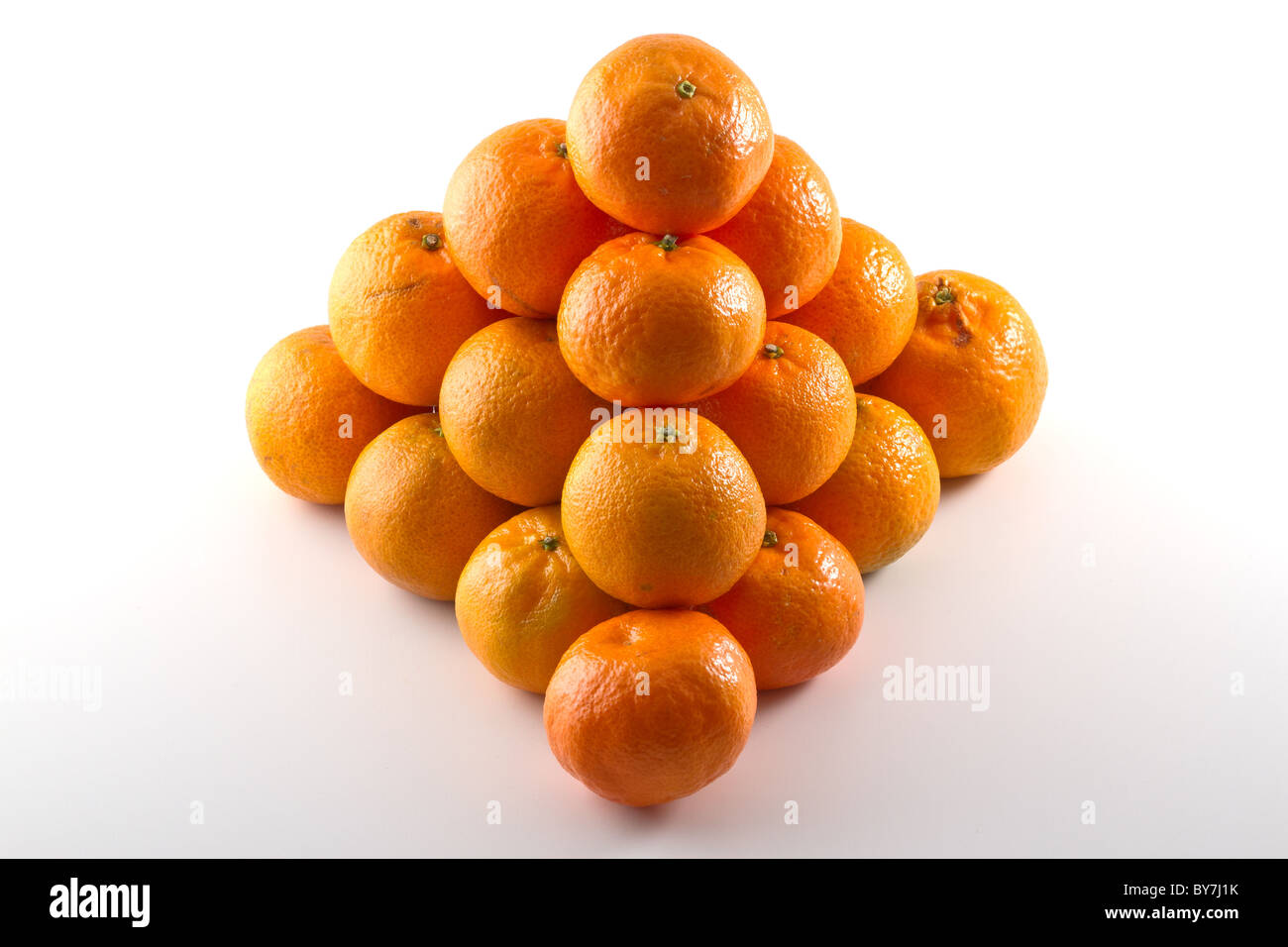 Clementines arranged in a pyramid shape isolated on white background - Stock Image
