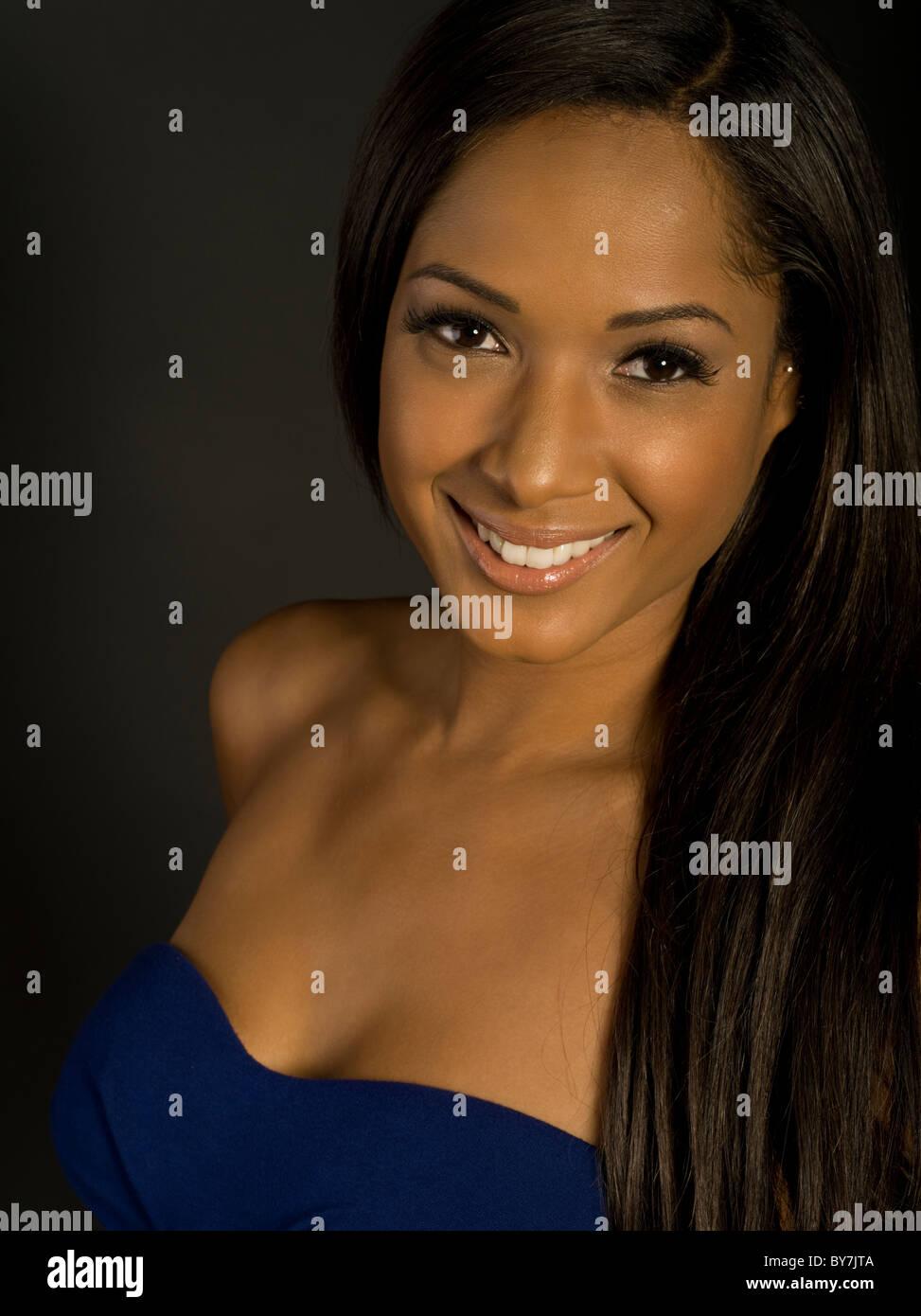 Studio Portrait beautiful woman thirties straight black hair smiling - Stock Image