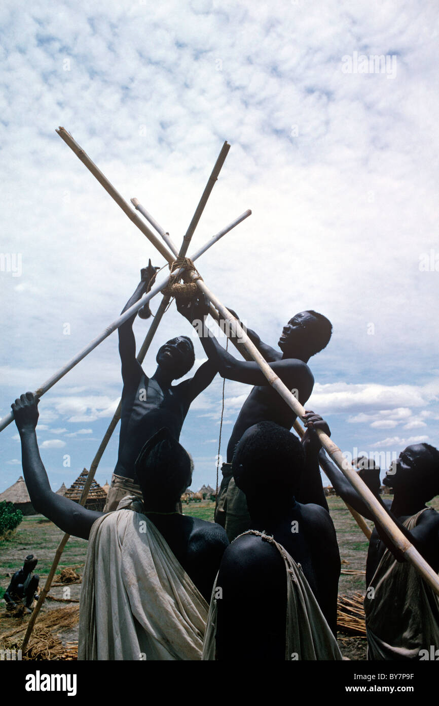 Constructing a traditional type hut at Malakal, Southern Sudan - South Sudan. Finished huts in the background. - Stock Image