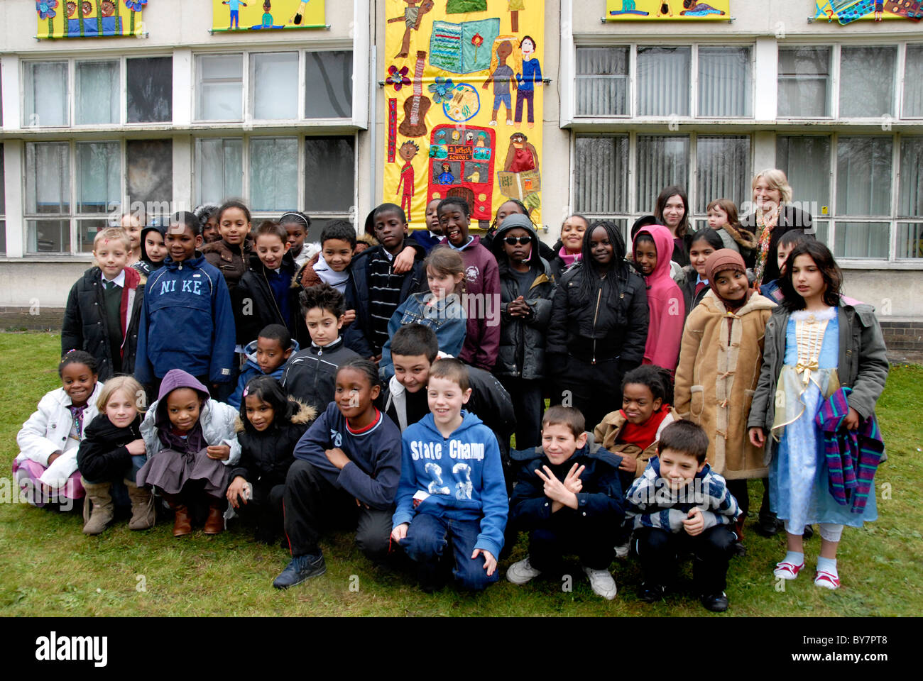 Mixed age group of junior school children assembled in front of school mural they have made. - Stock Image