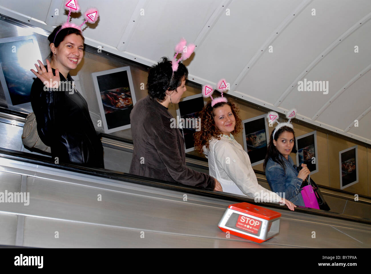 GROUP OF WOMEN ON HEN NIGHT TRAVELING ON TUBE WITH SILLY HEADBANDS - Stock Image