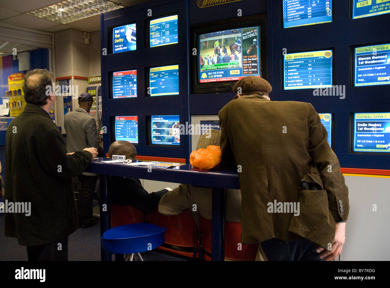 Men putting on betts in bookies - Stock Image