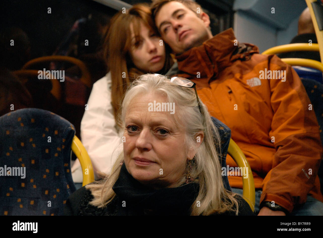 Middle aged Woman on bus with teenage couple behind - Stock Image
