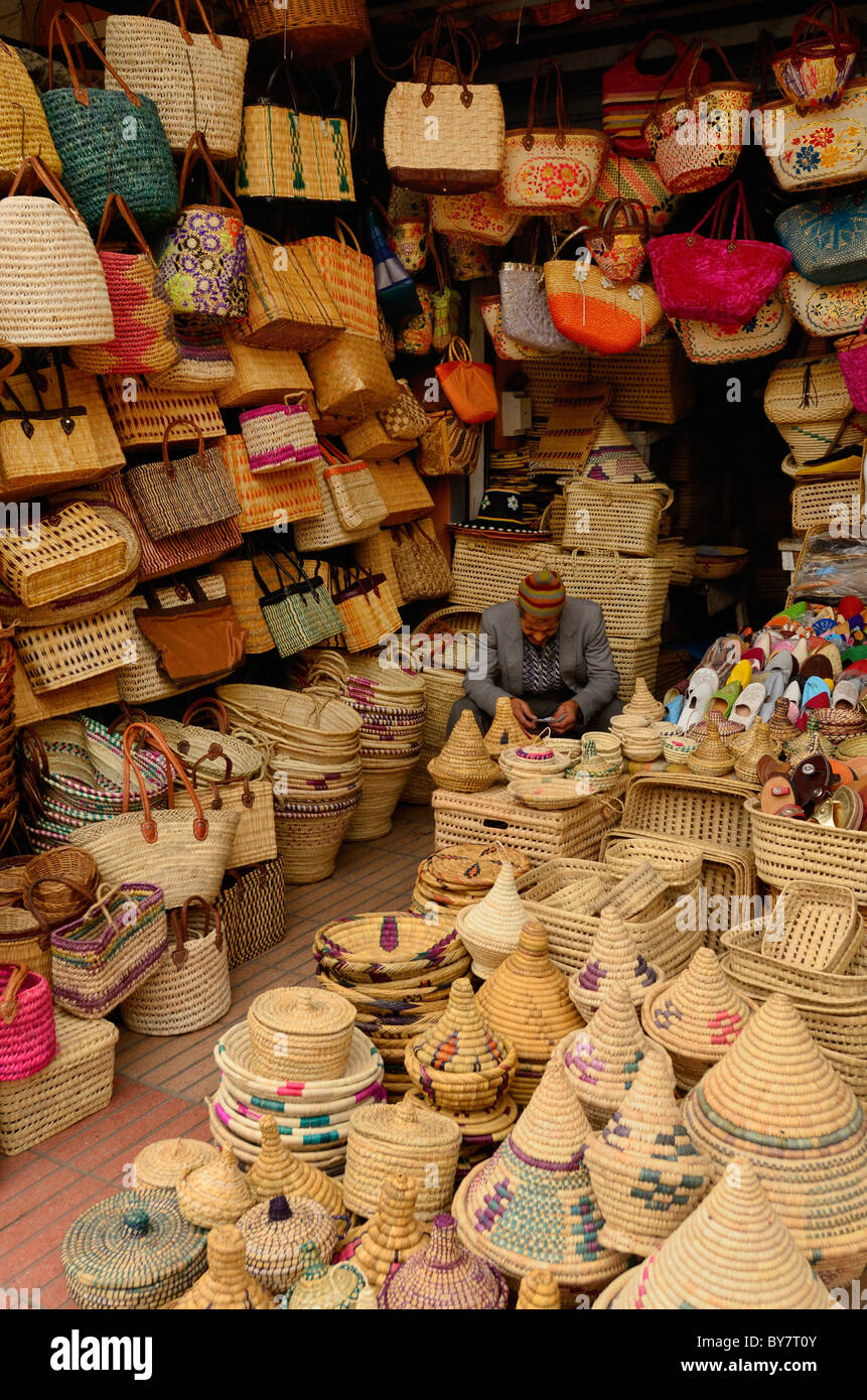 Shopkeeper selling basket weaving bags and containers in Casablanca new outdoor market Morocco - Stock Image