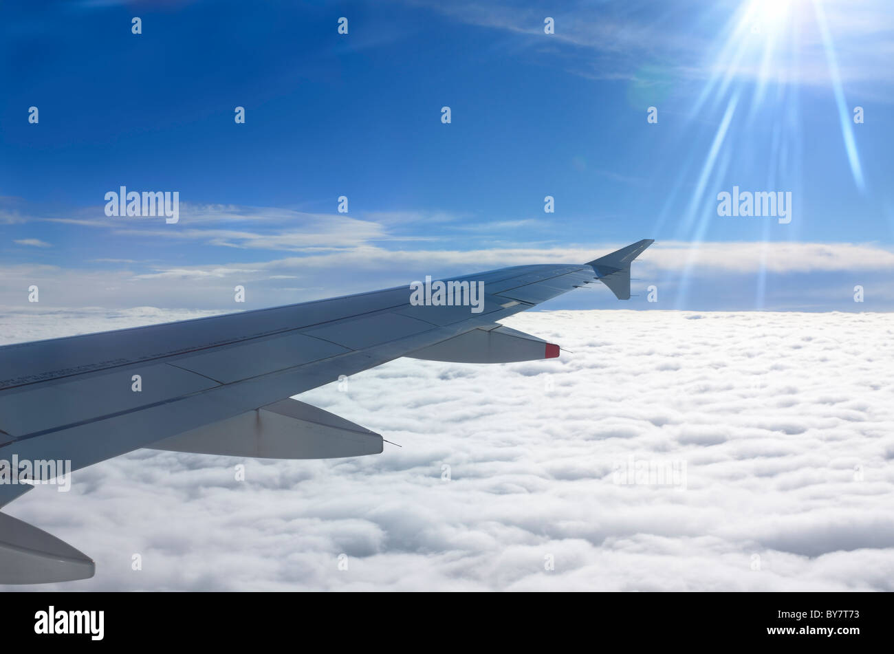 Flying above the clouds with jet aircraft wing and sun flare - Stock Image