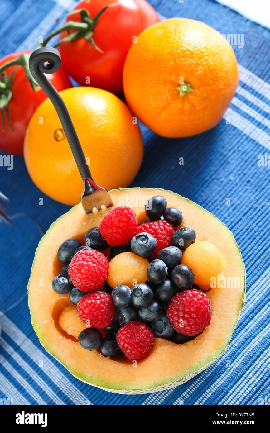 Mixed fruits inside cantaloupe bowl - Stock Image