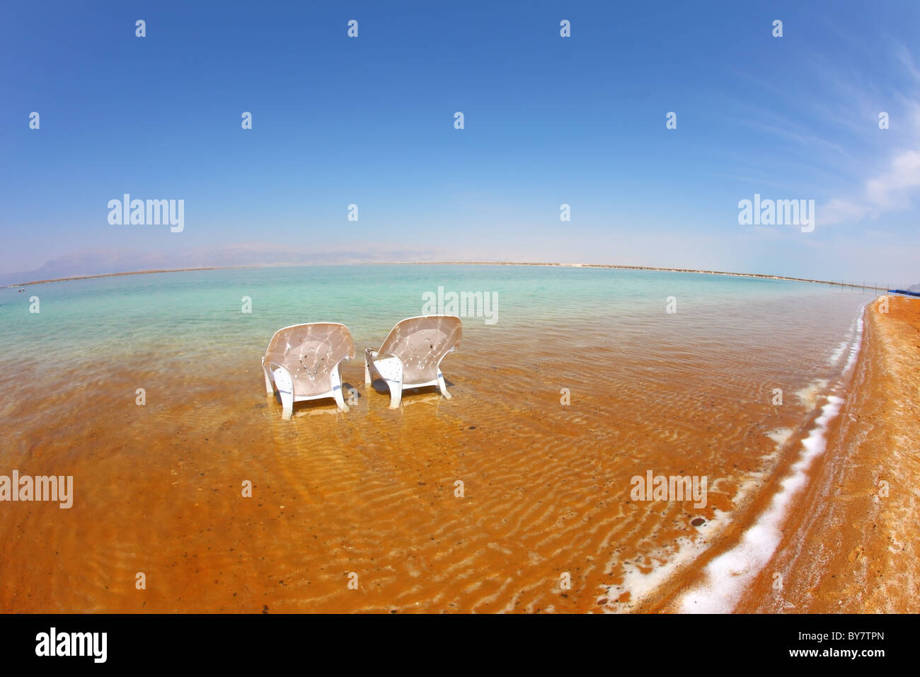 Two white beach chairs stood side by side in the clear water at the beach. Dead Sea, Israel - Stock Image