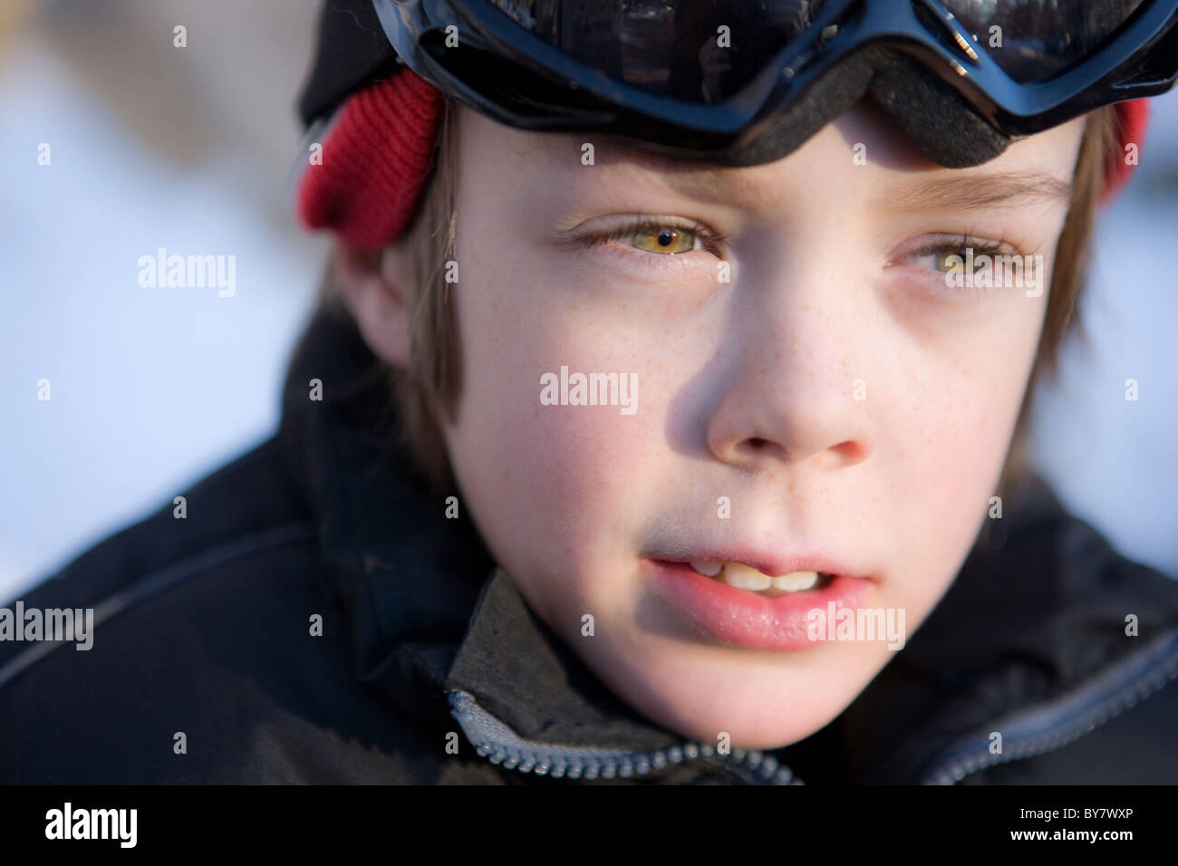 Boy dressed for skiing with anxious expression on his face. - Stock Image