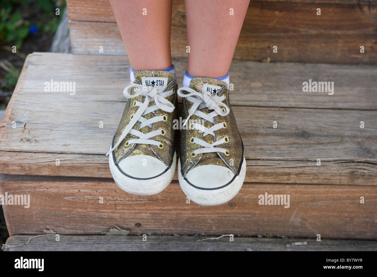 b77fc0a835eb close up of a girl wearing glitter gold converse all star sneakers - Stock  Image