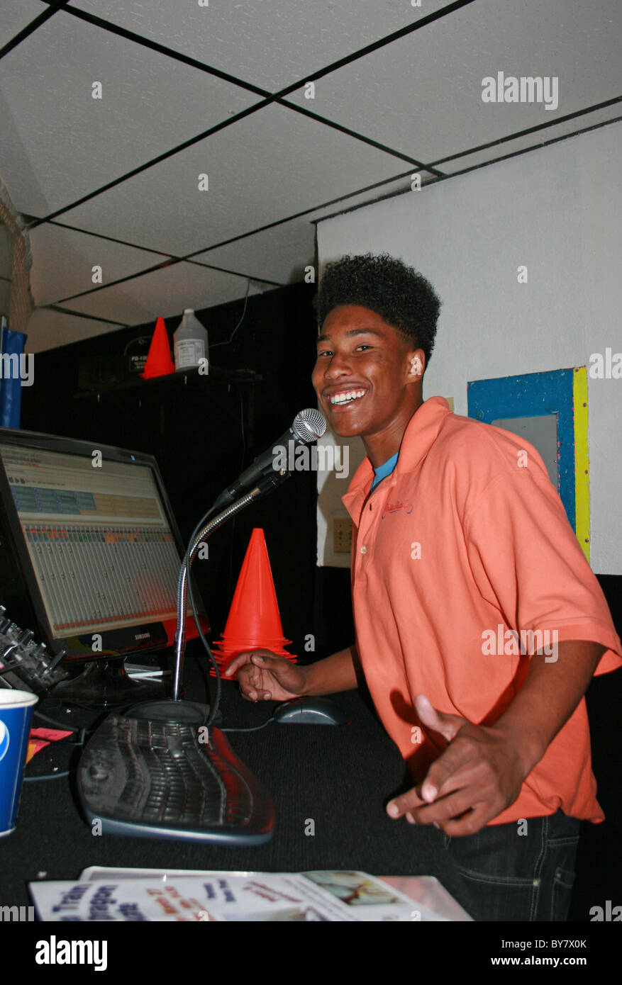 Teenager with an Eighties haircut DJing at a rollerskating rink. - Stock Image