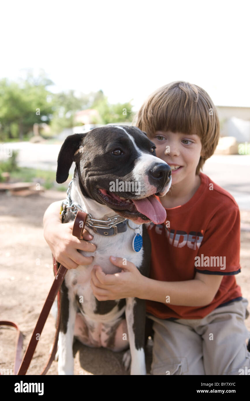 Boy affectionately hugging his dog outdoors. - Stock Image