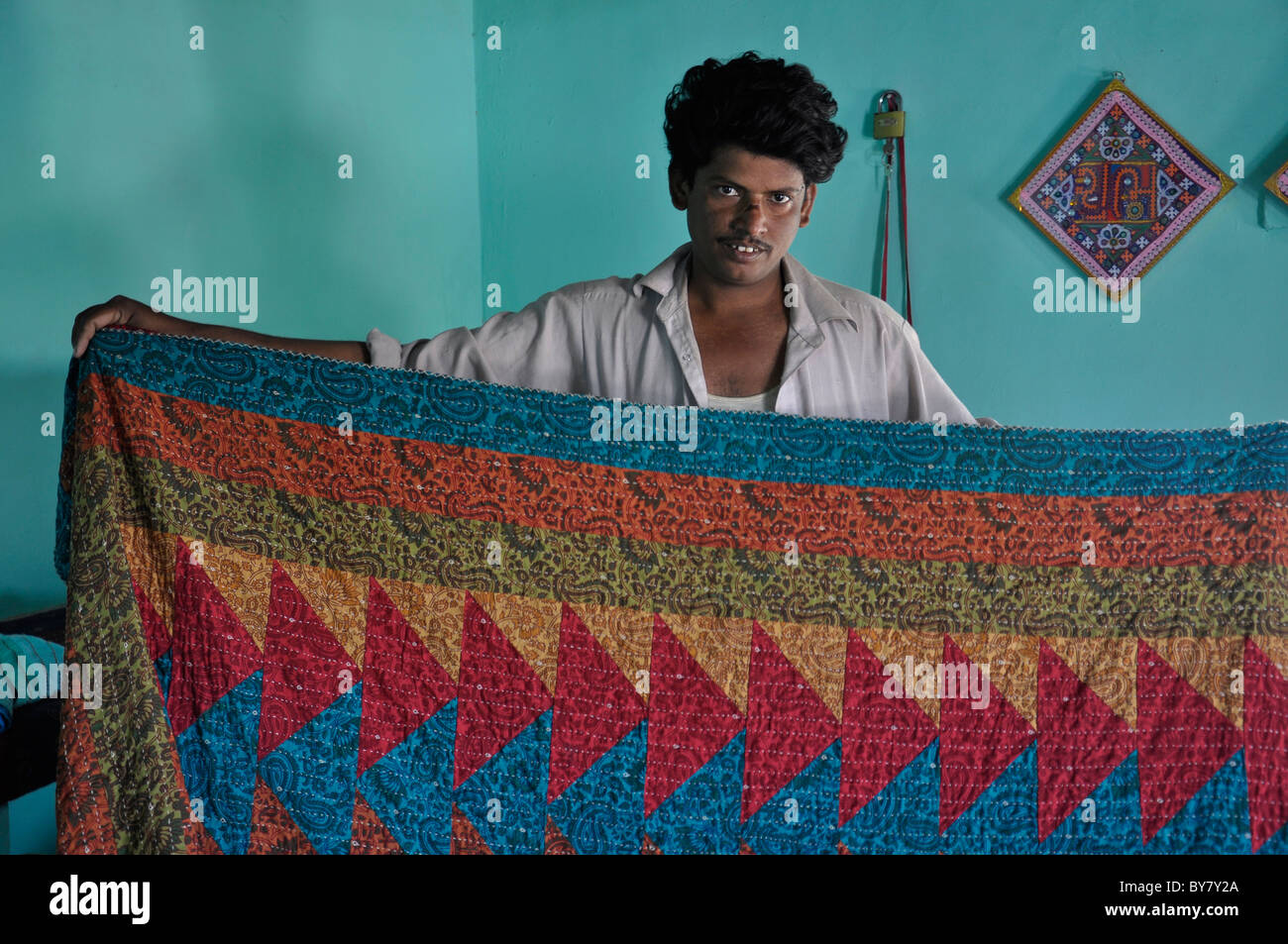 A man from Kutch, Gujarat showing his embroidery work on the bed sheet - Stock Image