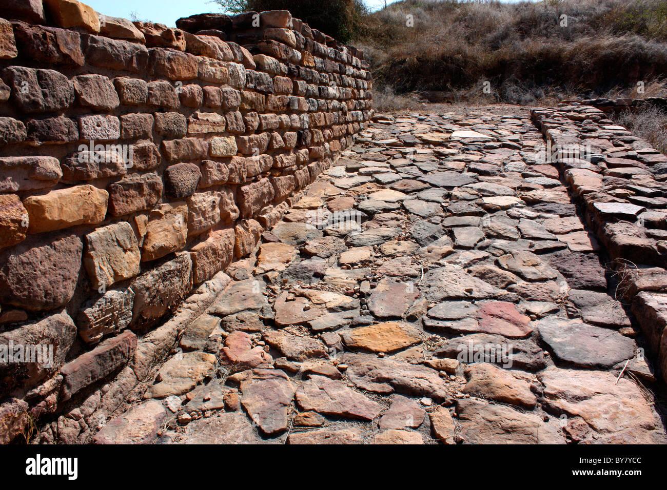 Road and brick wall of  ancient city-Ruins of Harappa civilisation, Dholavira, Gujarat, India - Stock Image