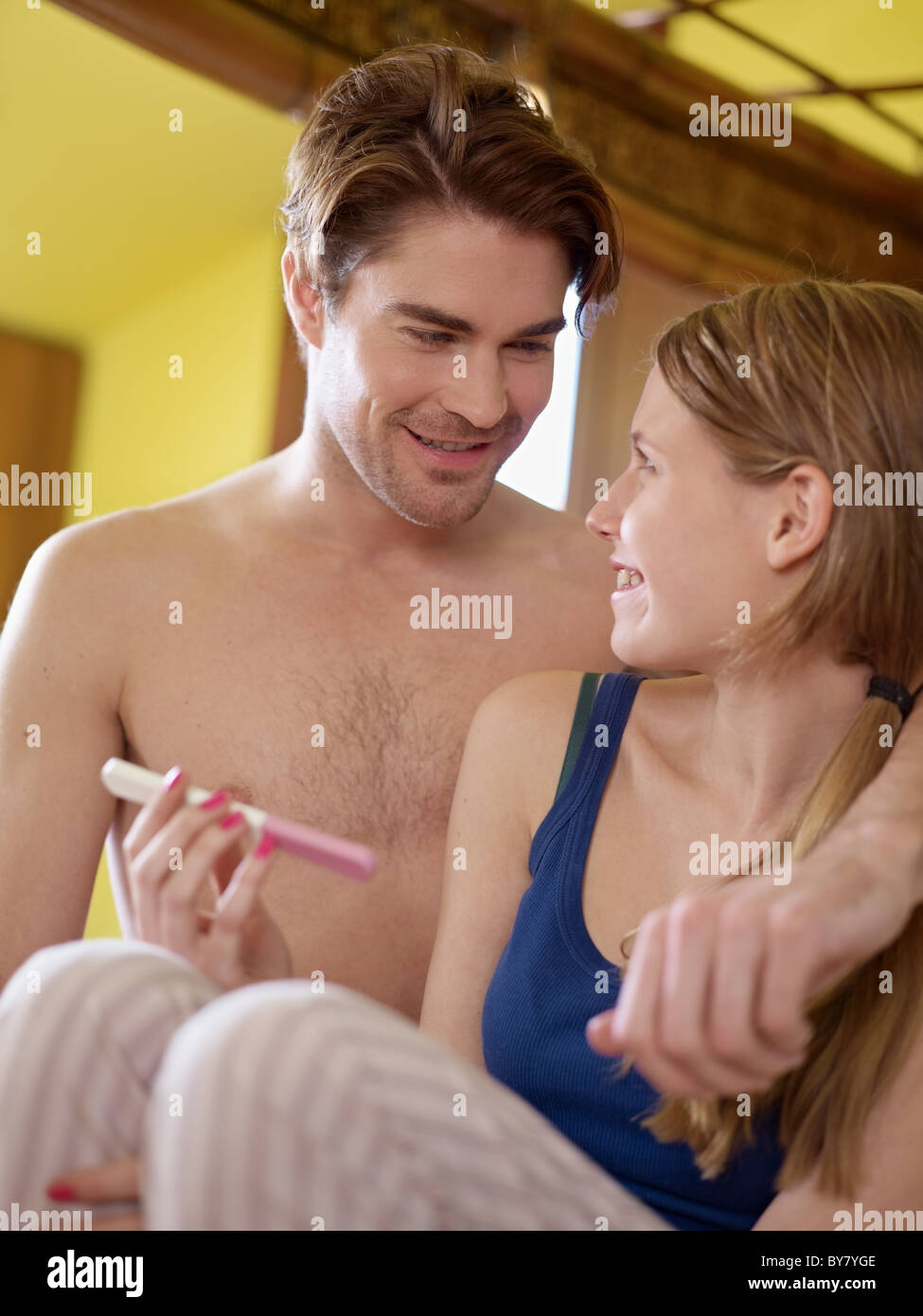 young caucasian woman in tanktop showing positive pregnancy test to her husband and smiling. - Stock Image