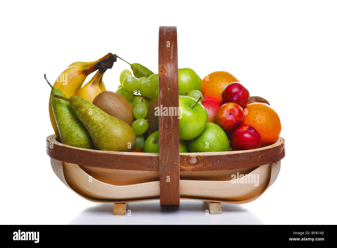 Photo of a wooden trug full of fresh fruit, isolated on a white background. Stock Photo