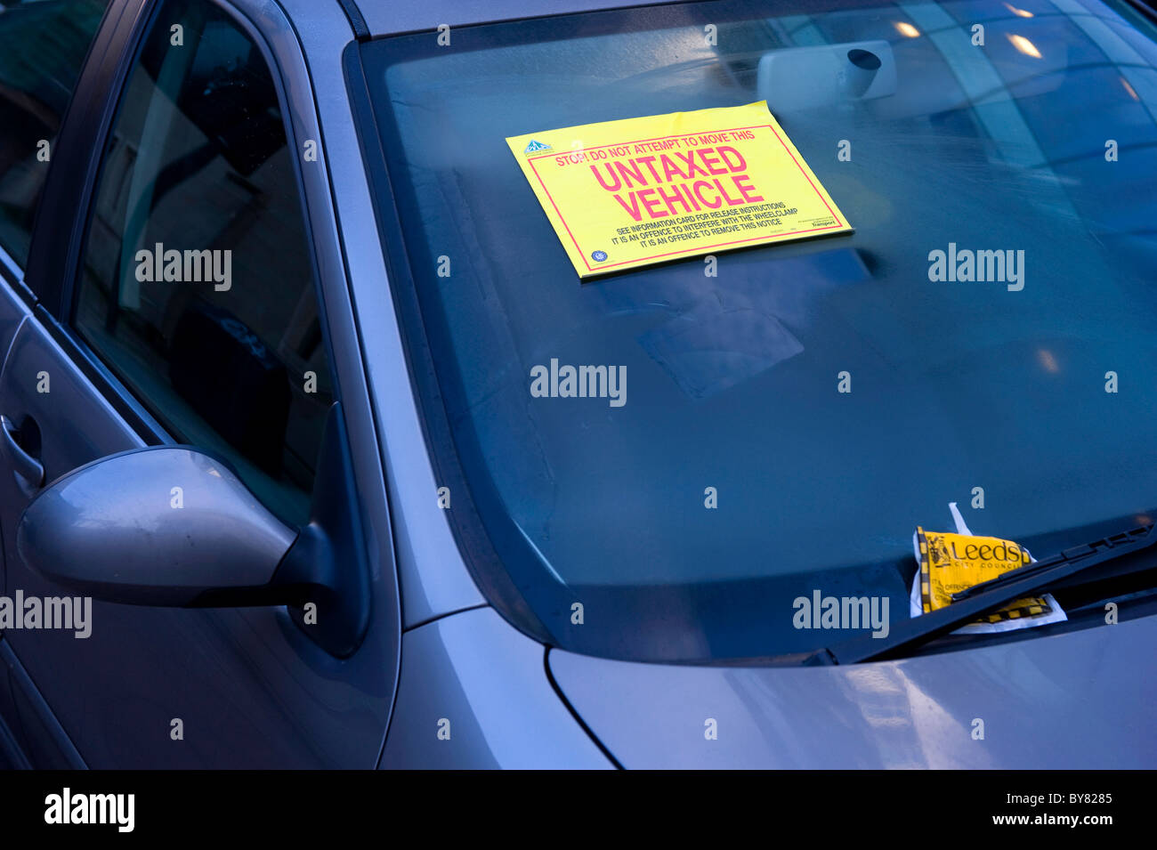 untaxed warning sticker attached to windscreen of vehicle warning not to move clamped vehicle uk Stock Photo