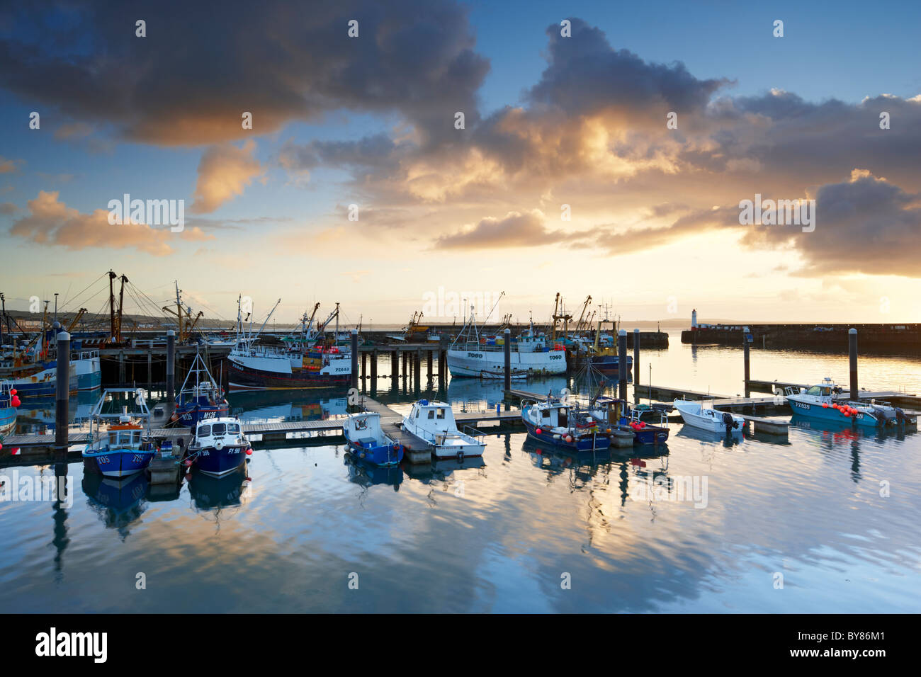 Dramatic rain clouds catching the light of dawn pass over and reflect in the calm waters of Newlyn Harbour - Stock Image