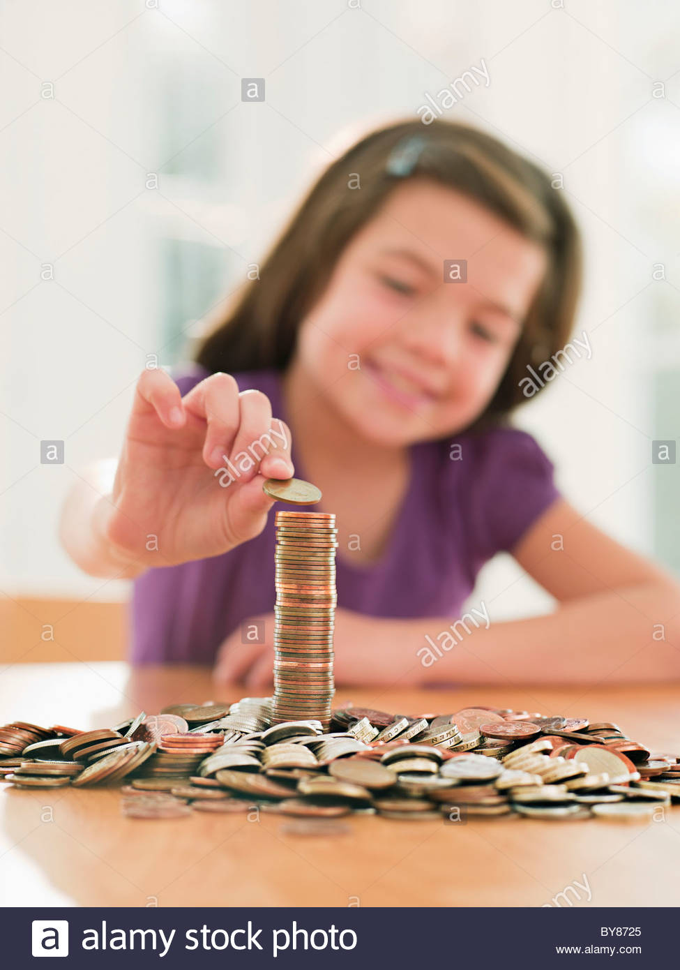 Smiling girl stacking coins - Stock Image