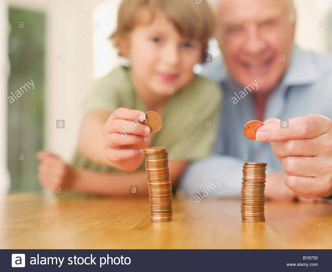 Grandfather and grandson stacking coins - Stock Image
