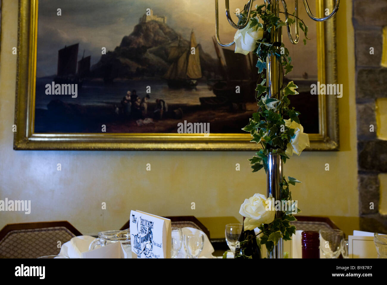 White roses and ivy centrepiece on dining table - Stock Image