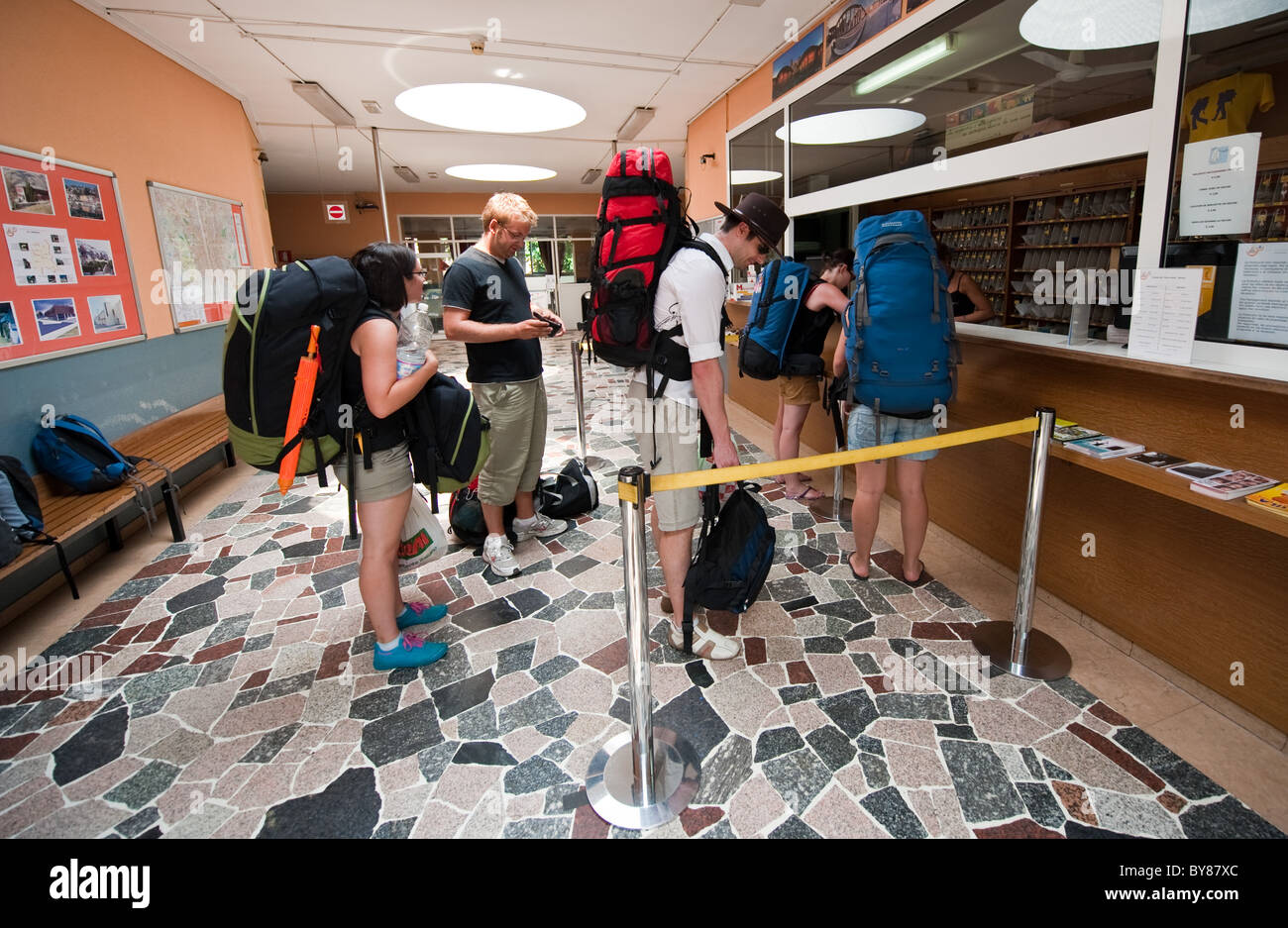 Backpackers check in at city Hostel, Milan, Italy - Stock Image