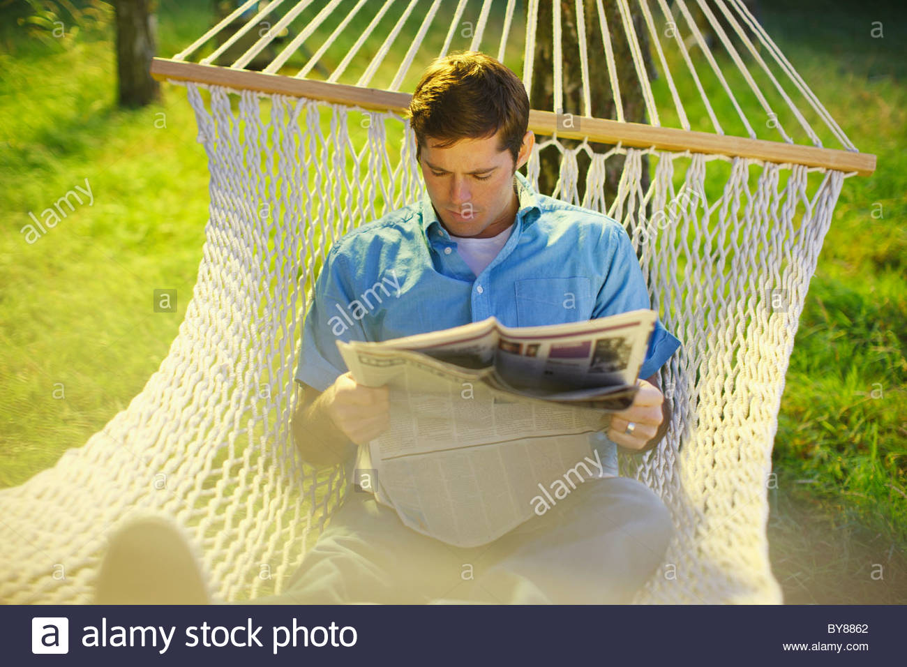Man laying in hammock reading newspaper - Stock Image
