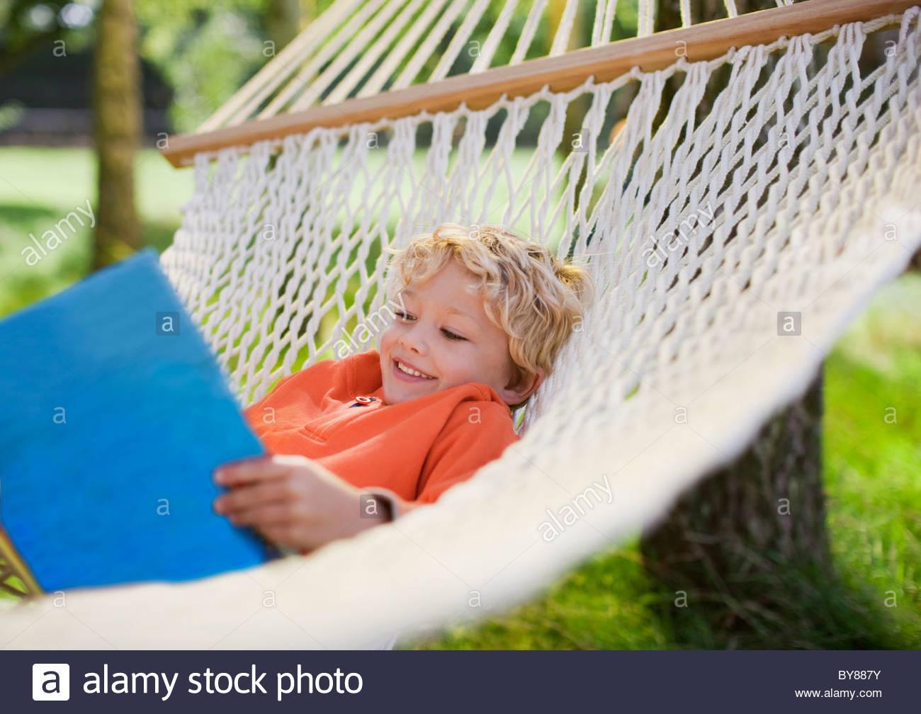 Boy laying in hammock reading book - Stock Image