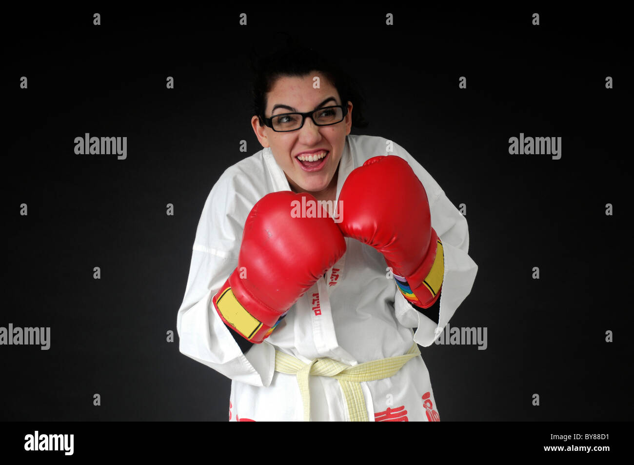 female Wimp tries to box On black Background - Stock Image