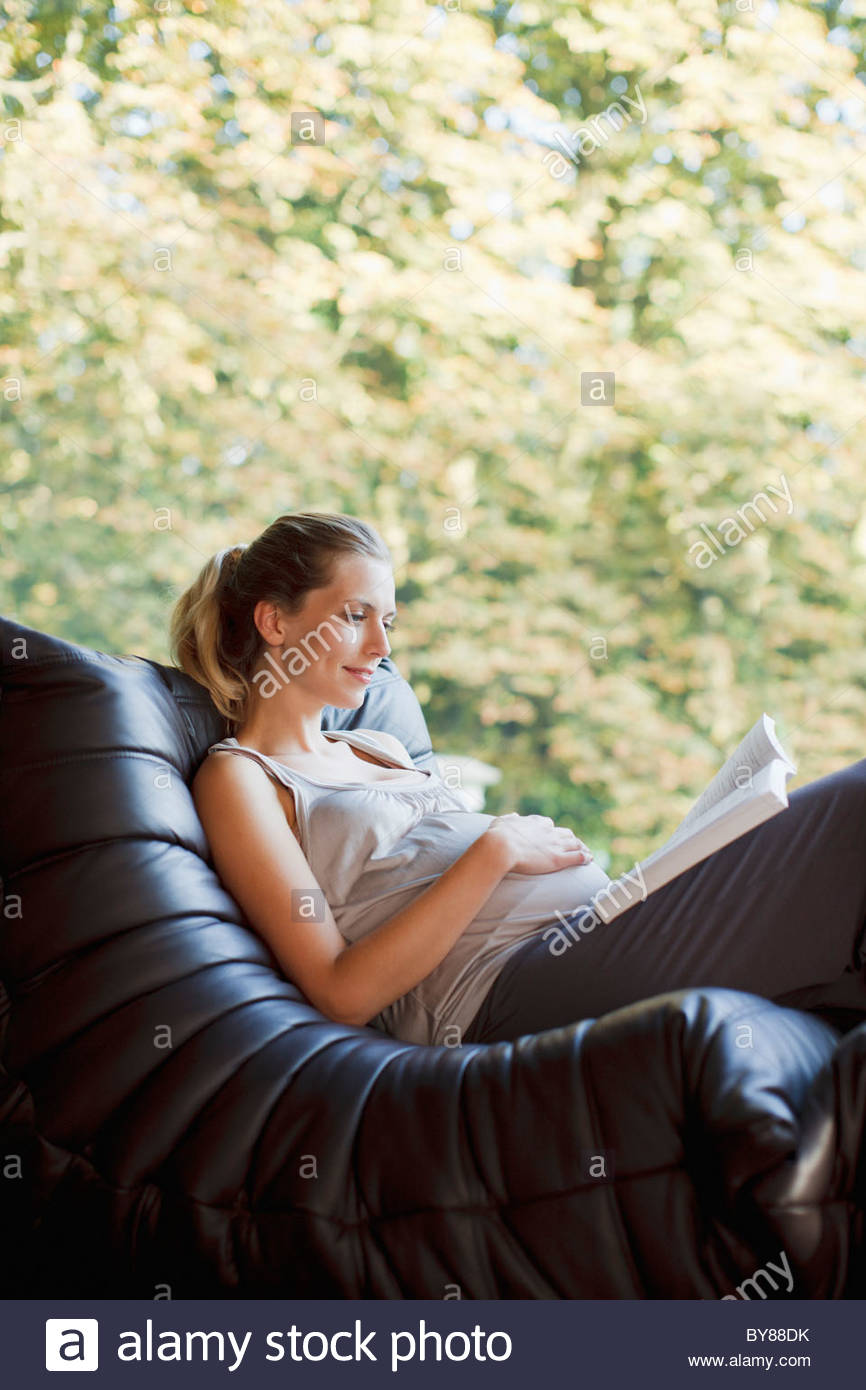 Pregnant woman reclining in chair reading book - Stock Image