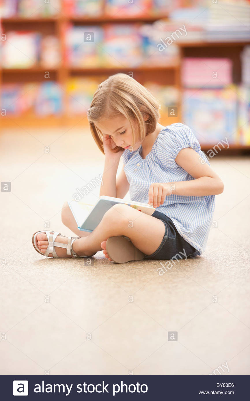 Girl sitting on floor reading book - Stock Image