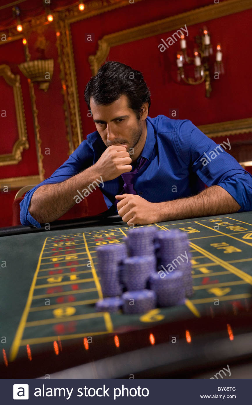 Anxious man looking at gambling chips in casino - Stock Image
