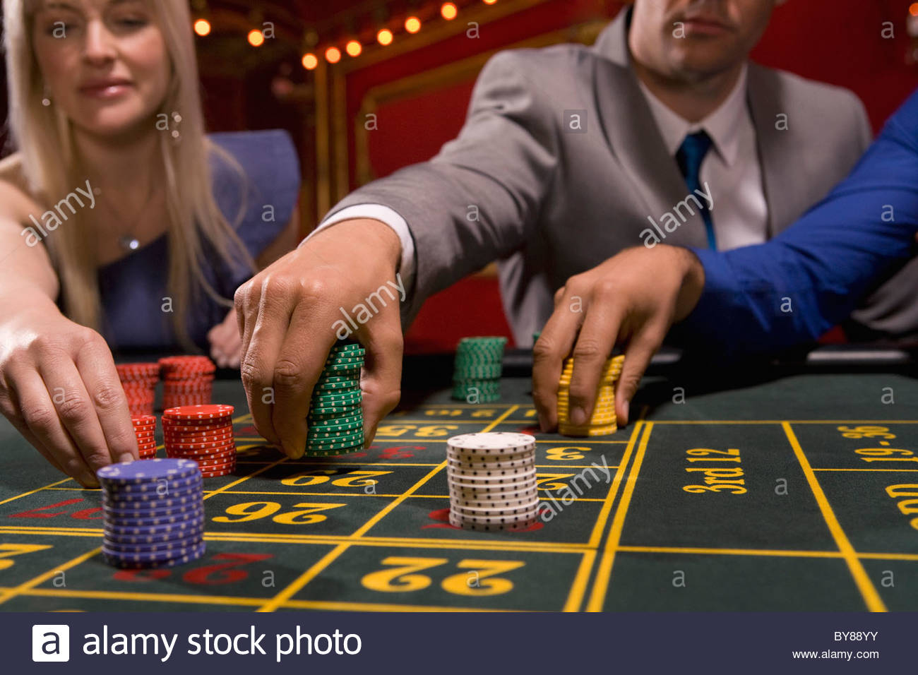 People placing bets with gambling chips - Stock Image