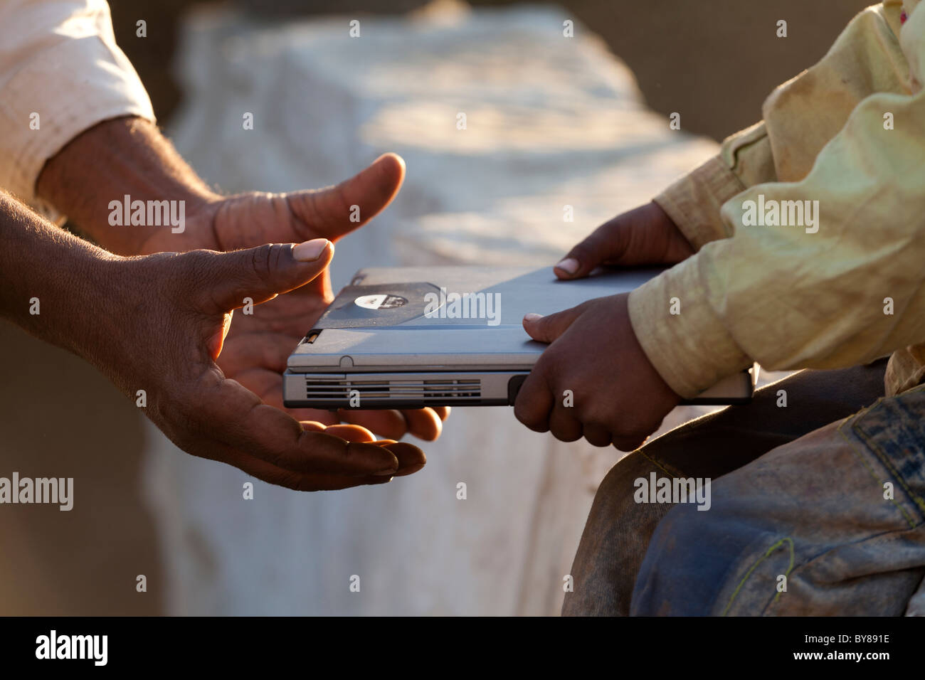 India, Rajasthan, Jodhpur, tribesman's hand about to receive laptop from young boy's hand - Stock Image