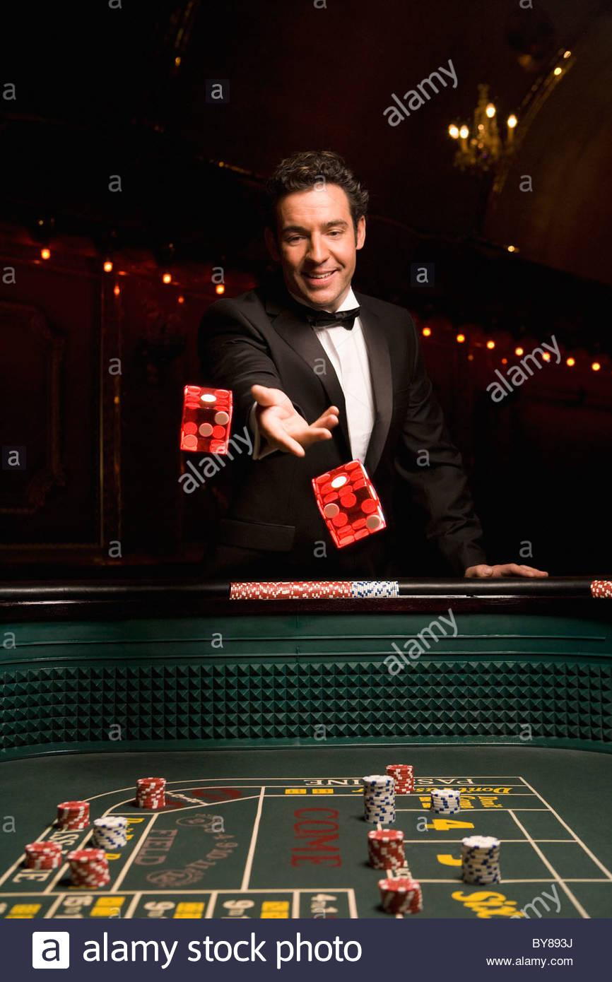 Man throwing dice at craps table - Stock Image