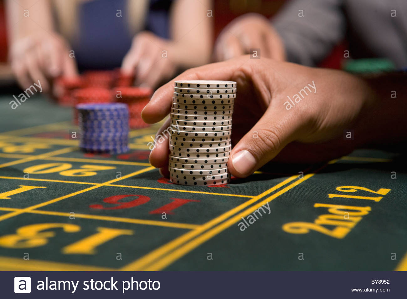 Man placing bet with gambling chips - Stock Image
