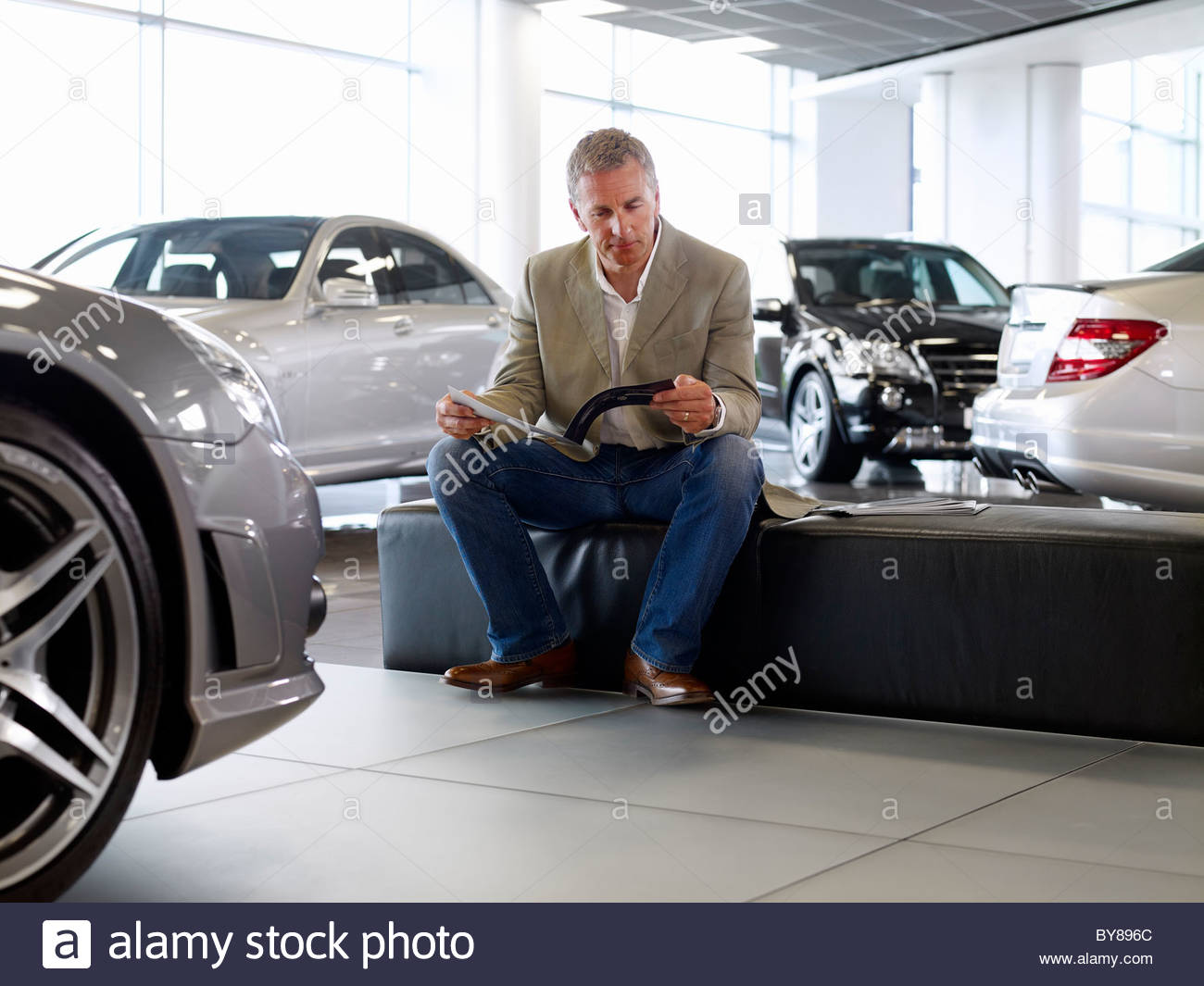 Man looking at brochure in automobile showroom Stock Photo