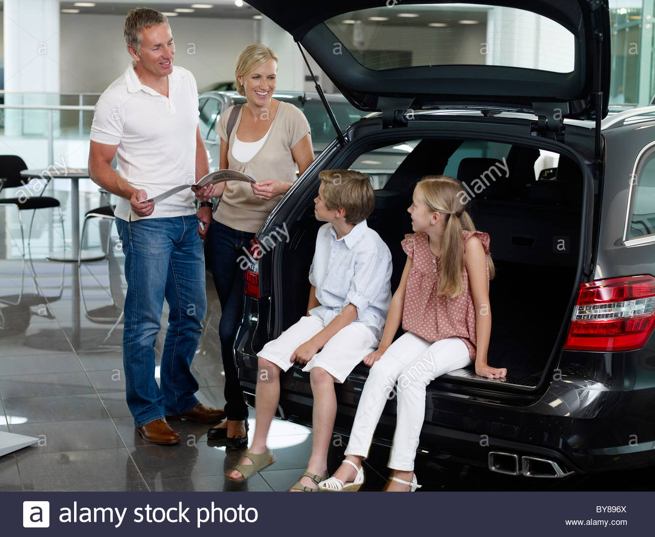 Family looking at new car in showroom - Stock Image