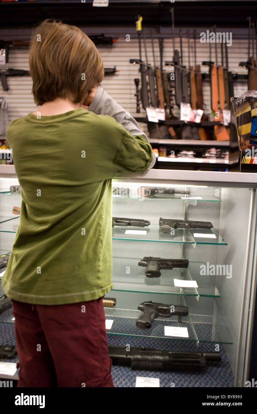 Boy looking at hand guns and rifle in a sporting goods store, United States - Stock Image
