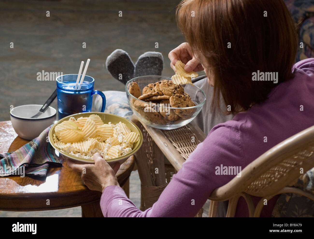 woman seated eating junk food - Stock Image