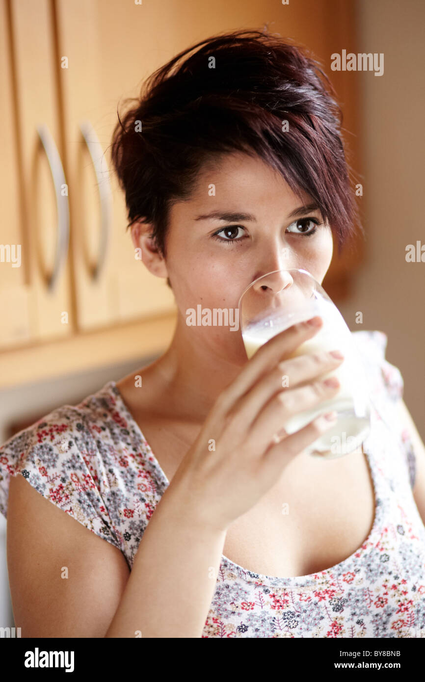Woman drinking glass of milk - Stock Image