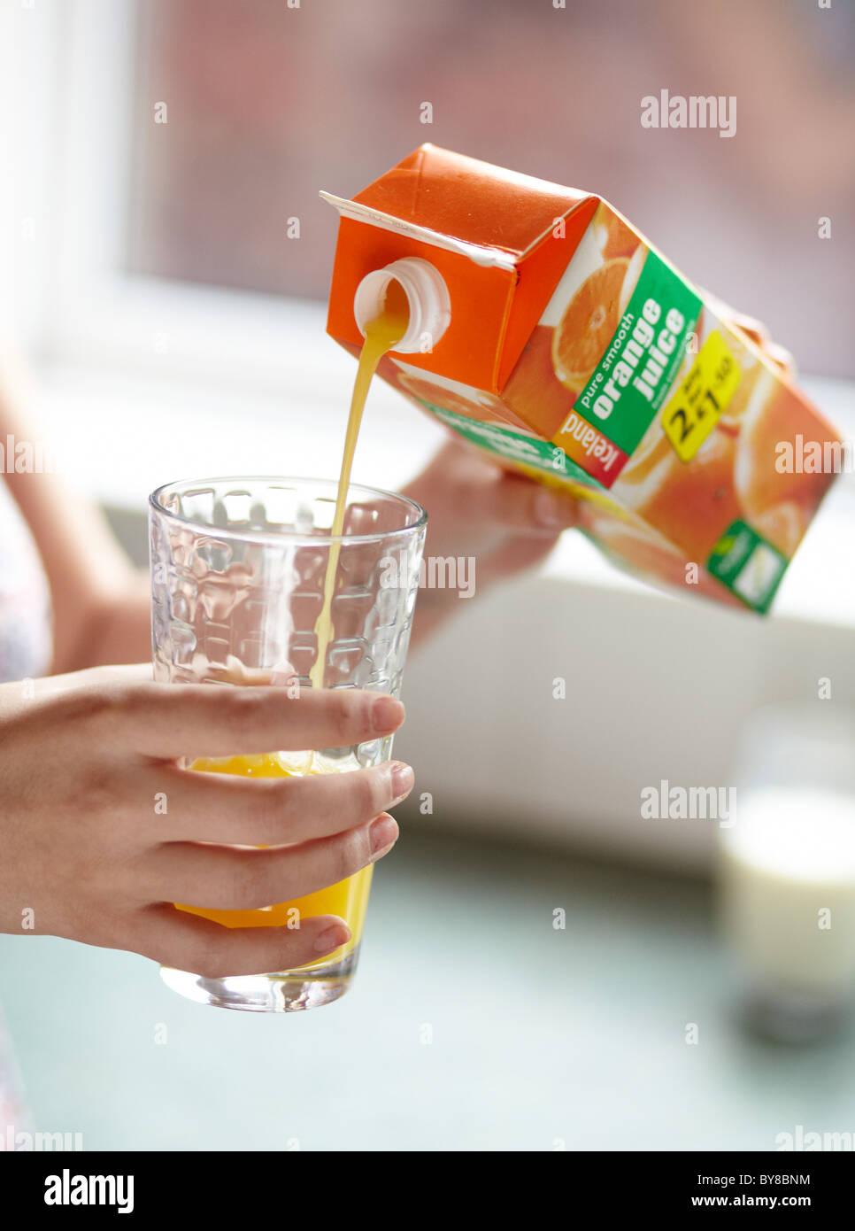 Girl pouring fresh orange juice - Stock Image