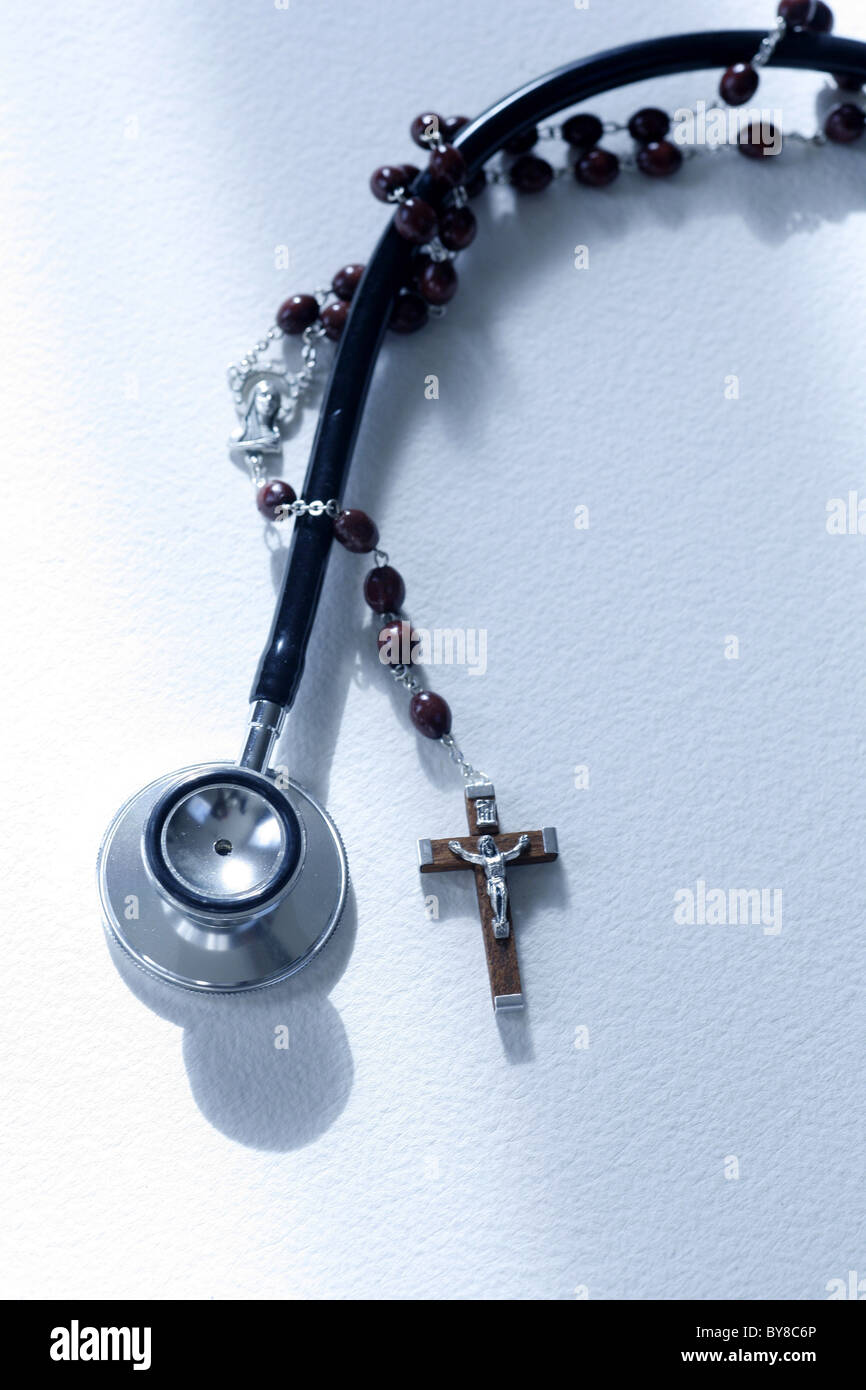 a stethoscope and a rosary entwined,  medical science versus the church or religion - Stock Image