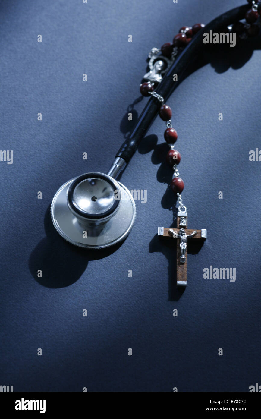 a stethoscope and a rosary entwined,  medical science versus religion - Stock Image