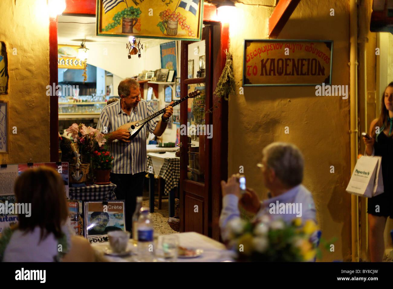 Man playing instrument, old venetian port, Rethymnon, Crete, Greece Stock Photo