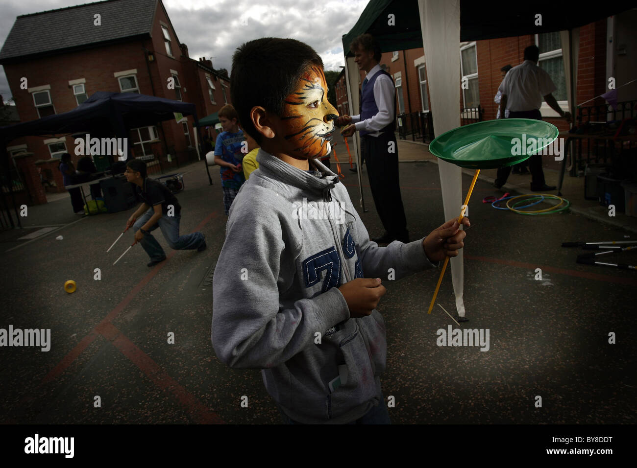 boy with painted face spins a plate at a fun day - Stock Image