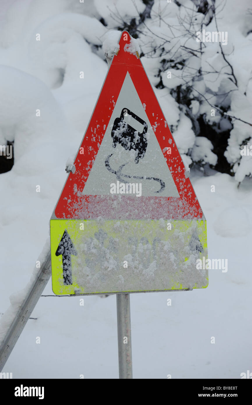 traffic sign warns of slippery snow and ice on road - Stock Image
