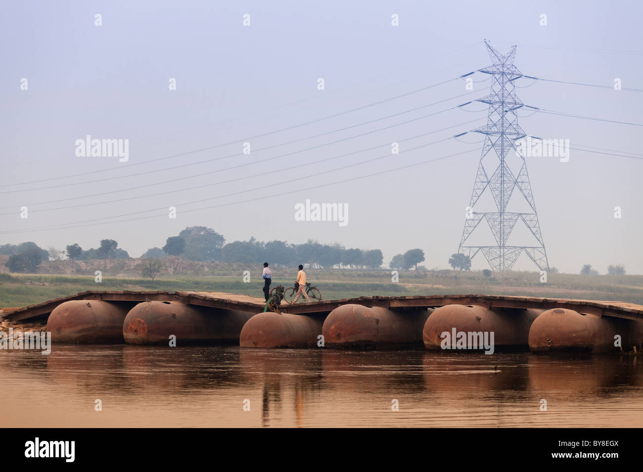 India, Uttar Pradesh, Agra, two men crossing pontoon bridge over Yamuna River - Stock Image