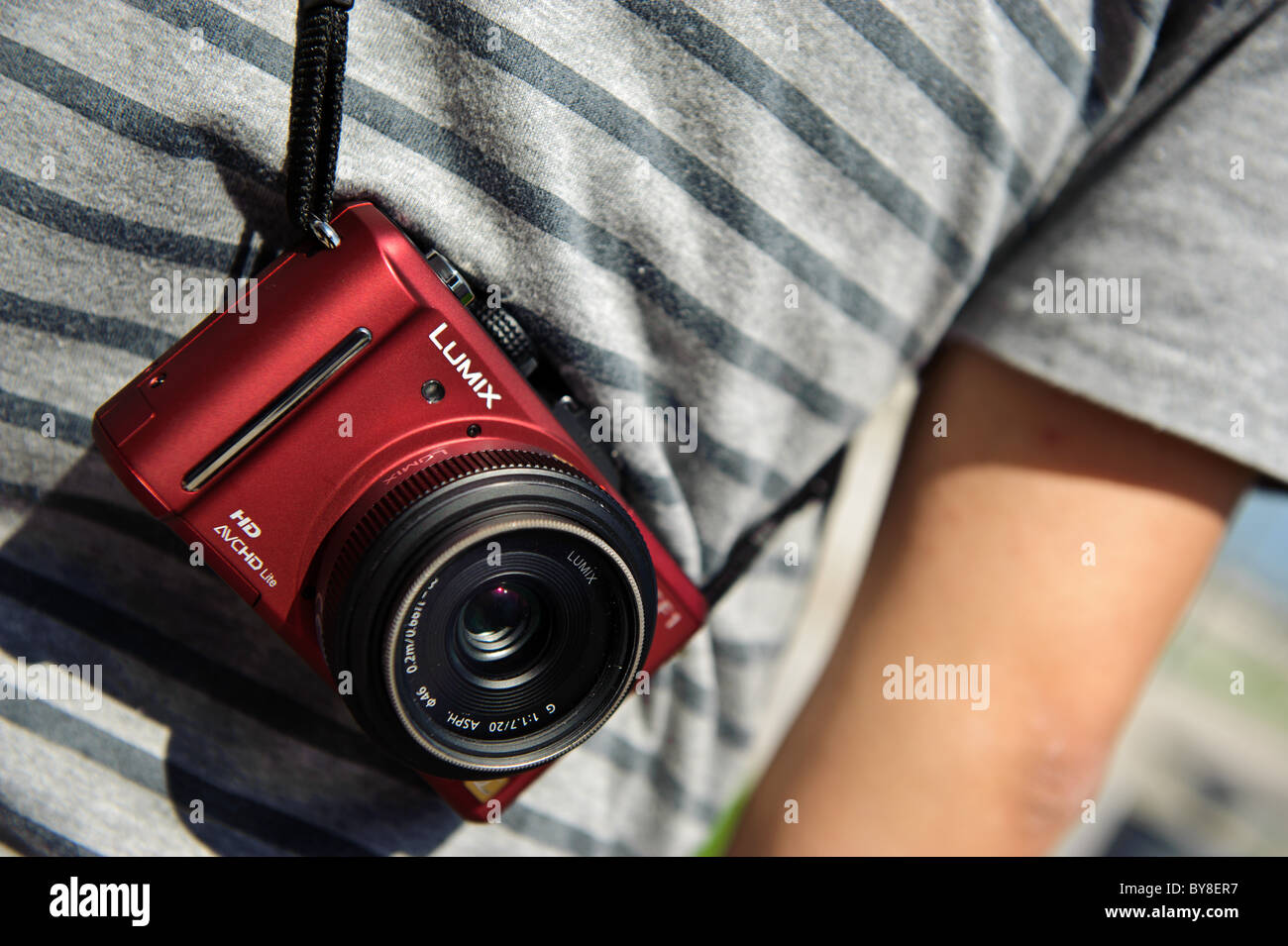 Photographer with a Lumix red camera - Stock Image