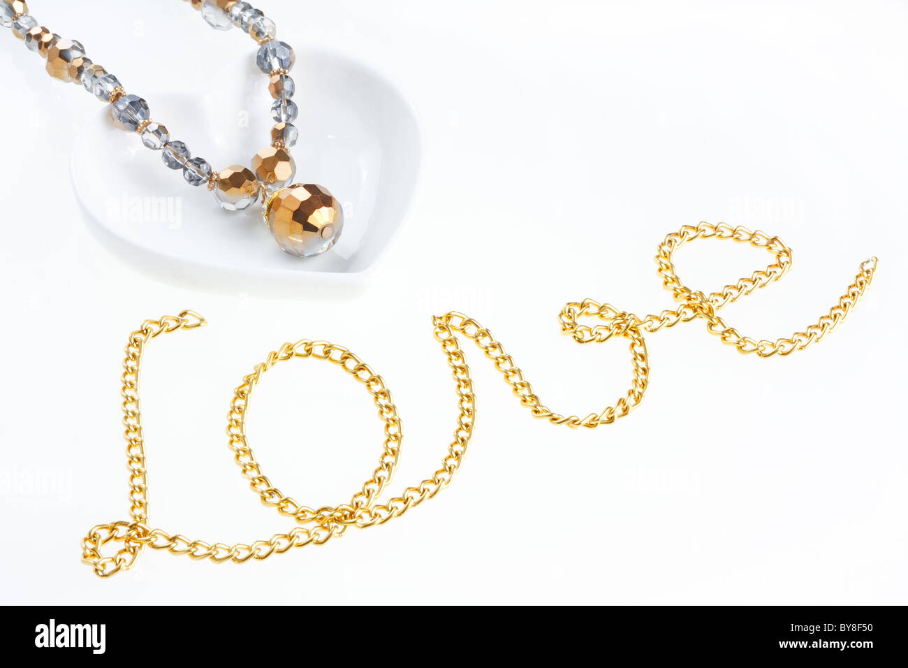 Jewel necklace on heart shaped saucer and yellow metal chain arranged in form of word 'Love' - Stock Image