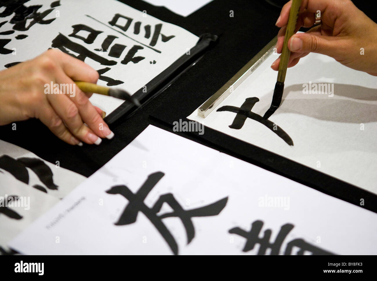 Students in a calligraphy class.  - Stock Image